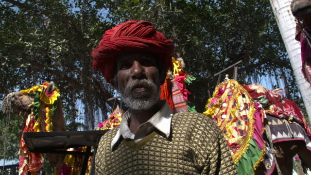 camel owner with red turban waiting for tourist - turban stock videos & royalty-free footage