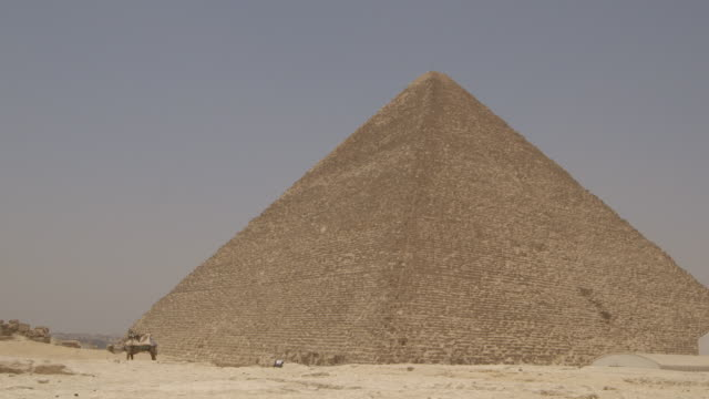 a camel stands and a man in traditional clothing sits in front of the pyramid of khufu, also known as the pyramid of cheops or the great pyramid of giza, egypt. - egypt stock videos & royalty-free footage
