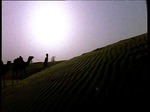 stockvideo's en b-roll-footage met camel train in silhouette walks up thar desert sand dunes, rajasthan - ruimte exploratie