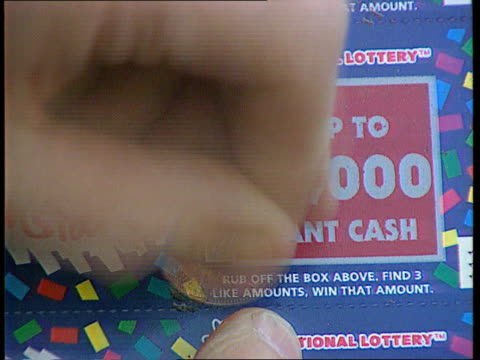 camelot directors payout; itn lib seq national lottery scratchcard being scratched - scratch card stock videos & royalty-free footage