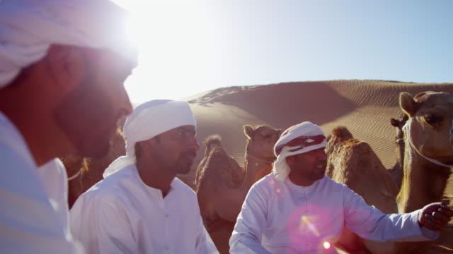 vídeos de stock, filmes e b-roll de camels and handlers travelling across desert sand dunes - adereço de cabeça