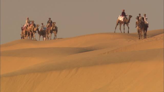 vídeos de stock, filmes e b-roll de camels and their riders traverse the desert landscape. - montar um animal