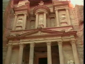 camels lie in the shaded red dirt beneath the ancient, roman-inspired carved temple of petra in jordan. - アラバ砂漠点の映像素材/bロール