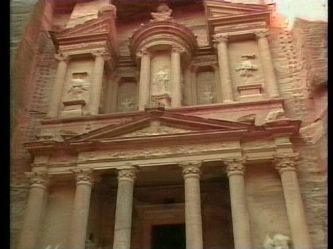 camels lie in the shaded red dirt beneath the ancient, roman-inspired carved temple of petra in jordan. - red rocks stock videos & royalty-free footage