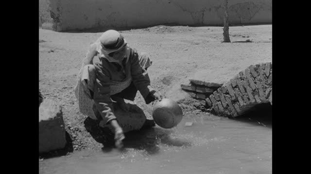 camels walking in village street iranian woman in traditional clothing washing bowl in stagnet water baby in shirt walking bg - iran bildbanksvideor och videomaterial från bakom kulisserna