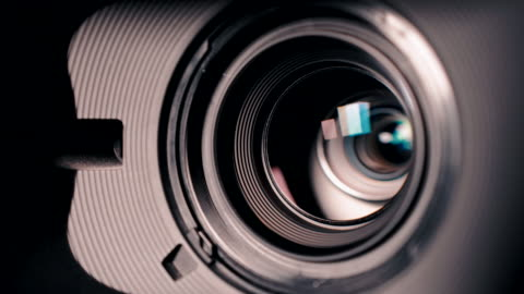camera and lens zoom, close-up photo, closeup shot of professional video camera, with its lens zooming in and out. - film camera stock videos & royalty-free footage