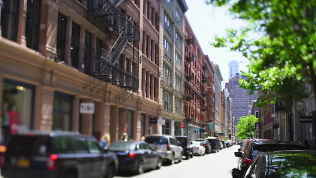 camera captured rows of loft buildings along the street beside the fresh green trees in soho district at new york city ny usa on may 18 2019. cars run on the street and people walk on the sidewalk under the fresh green trees. - loft video stock e b–roll