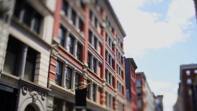 stockvideo's en b-roll-footage met camera captured rows of loft buildings along the street in soho district at new york city ny usa on may 16 2019. cars run on the street. - loft