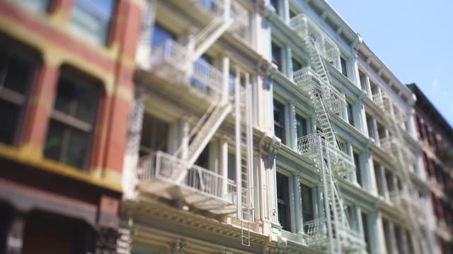 camera captured rows of loft buildings along the street in soho district at new york city ny usa on may 16 2019. cars run on the street. - fire escape stock videos and b-roll footage