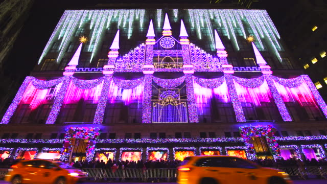 Camera captures 2016 Saks Fifth Avenue Holiday Light Show and crowd at front of Saks Fifth Avenue window displays, which are illuminated at night in Midtown Manhattan. Cars run on Snow covered 5th Avenue.