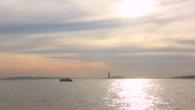 Camera captures a ferryboat which runs on brilliant New York Bay at sunset. Statue of Liberty and Ellis Island can be seen behind.