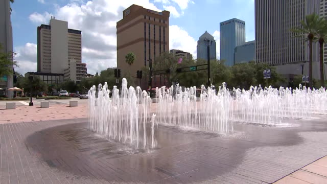 a camera captures an establishing shot of the fountains outside of the park tower skyscraper in the downtown area of tampa florida - aerial or drone pov or scenics or nature or cityscape stock videos & royalty-free footage