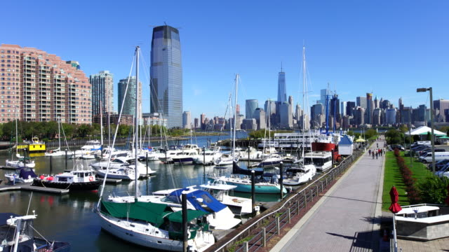 camera captures anchored ships and hi-rise residential buildings at liberty harbor marina. manhattan skyscrapers can be seen at opposite shore of hudson river from liberty state park - jachthafen stock-videos und b-roll-filmmaterial