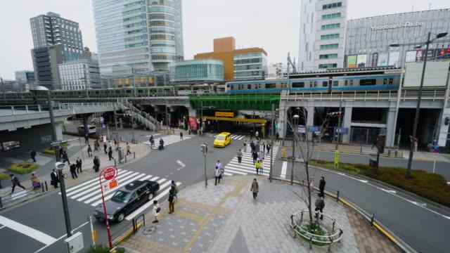 Camera captures at front of Akihabara Station West from The Akiba Bridge in Akihabara, Chiyoda-ku Tokyo. Yamanote Line and Keihin-Tohoku Line run on elevated railroad at JR Akihabara Station.