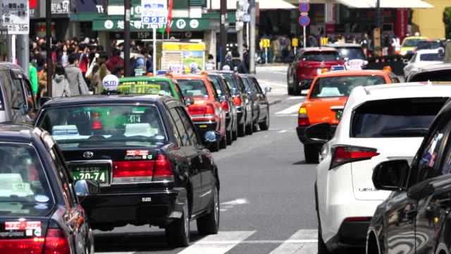 camera captures city traffic in front of ikebukuro station east entrance at meiji-dori ikebukuro, toshima-ku tokyo. - タクシー点の映像素材/bロール