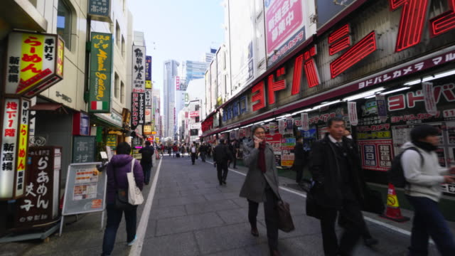 Camera captures cityscape of Shinjuku Station West Entrance district. The are many appliance stores, Camera shops and Restaurants.