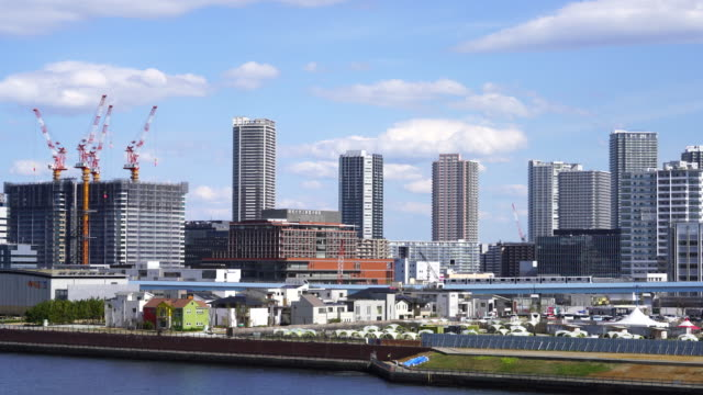 Camera captures cityscape of Toyosu District in Koto, Tokyo, from Harumi Ohashi Bridge. Tokyo Waterfront New Transit Yurikamome Line run on elevated railroad.