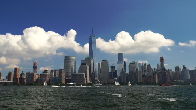 Camera captures cloudscape above the Manhattan skyscrapers through over the Hudson River.  Ships run on Hudson River.