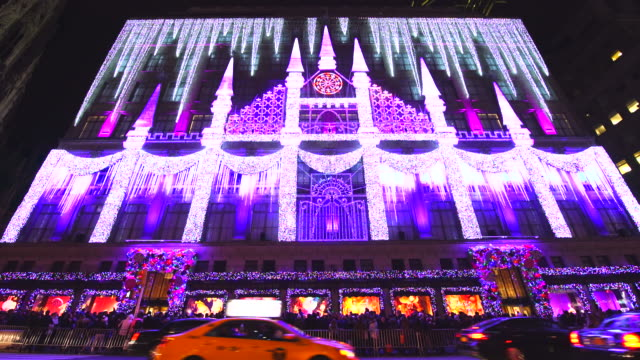 camera captures complete 2016 saks fifth avenue holiday light show and crowd at front of saks fifth avenue window displays, which are illuminated at night in midtown manhattan. cars run on snow covered 5th avenue. - facade stock videos & royalty-free footage