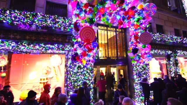 PAN Camera captures crowd at front of Saks Fifth Avenue window displays, which are illuminated by 2016 Saks Fifth Avenue Holiday Light Show at night in Midtown Manhattan.