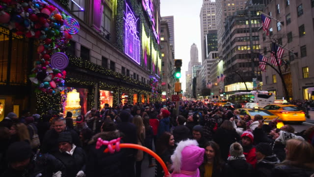 PAN Camera captures crowd at front of Saks Fifth Avenue window displays and other side of 5th Avenue at Rockefeller Center ward, which are illuminated by 2016 Saks Fifth Avenue Holiday Light Show at DUSK in Midtown Manhattan.