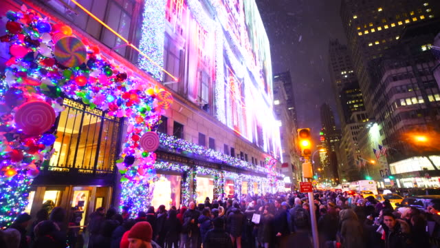 Camera captures crowd at front of Saks Fifth Avenue window displays during the snow, which are illuminated by 2016 Saks Fifth Avenue Holiday Light Show at night in Midtown Manhattan.
