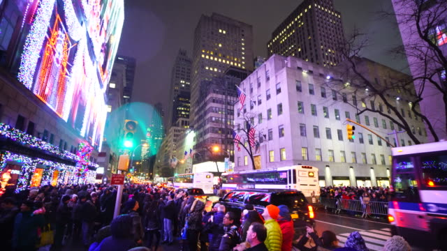pan camera captures crowd at front of saks fifth avenue window displays and other side of 5th avenue at rockefeller center ward, which are illuminated by 2016 saks fifth avenue holiday light show during the snow night in midtown manhattan. - rockefeller center christmas tree stock videos & royalty-free footage