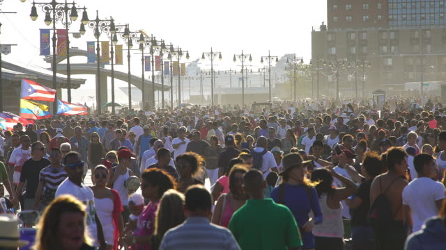 PAN Camera captures crowd who walks down the Coney Island Boardwalk. One large cruise ship runs on the sea behind crowd.