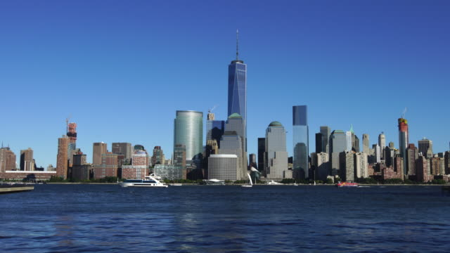 Camera captures cruise ships and Manhattan skyscrapers from New Jersey waterfront residential district.