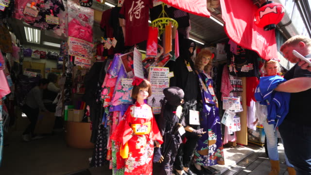 Camera captures display dolls in front of traditional gift shop at Nakamise-dori, which are wearing the Yukata (Japanese Casual Summer Kimono) and Ninja Costume.