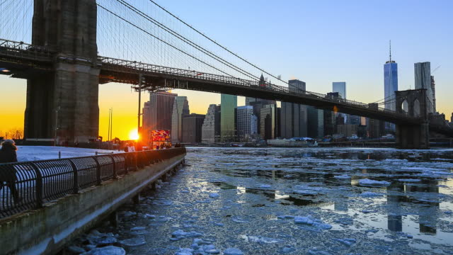 tl tu camera captures drifting ice under the brooklyn bridge at east river at from dusk to night.downtown manhattan skyscrapers can be seen behind brooklyn bridge.downtown manhattan skyscrapers and brooklyn bridge are reflected in the east river. - dusk to night stock videos and b-roll footage