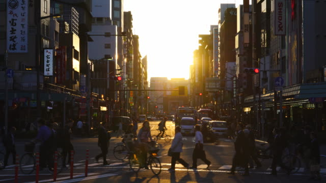 Camera captures evening commute scene at Kaminarimon-Dori at sunset in Asakusa, Taito-ku Tokyo. Sunset illuminates the Kaminarimon-Dori Street and buildings.