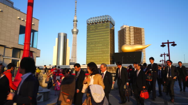 camera captures evening commuters at azumabshi bridge in asakusa ward tokyo.  sunset illuminates commuters and tokyo sky tree and downtown cityscape behind. - スカイツリー点の映像素材/bロール
