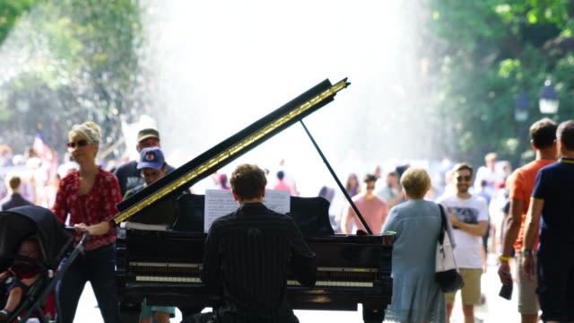 Camera captures fountain, trees, and people around there, which are illuminated by sunlight at Washington Square Park at Manhattan New York City. A pianist plays the piano at the park.