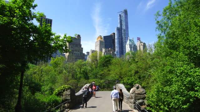 Camera captures Gapstow Bridge at Central PARK, which is surrounded by fresh green trees.Midtown Manhattan skyscrapers can be seen behind.