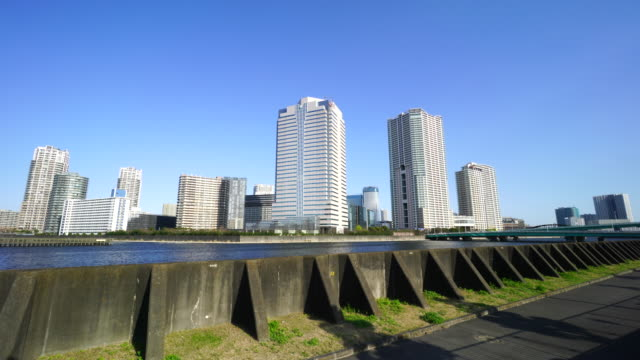 Camera captures high-rise buildings at Toyosu, Koto ward beyond the Harumi Canal Bank. Harumibashi Bridge can be seen in right side, which is over the canal and connects Tsukishima, Chuo ward and Toyosu, Koto ward.