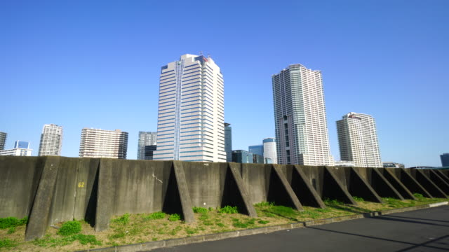 Camera captures high-rise buildings at Toyosu, Koto ward Tokyo beyond Harumi Canal Bank.