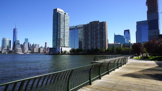 PAN Camera captures Manhattan skyscrapers behind New Jersey high-rise buildings. Newport district residential area can be seen beside the boardwalk at Jersey City New Jersey.