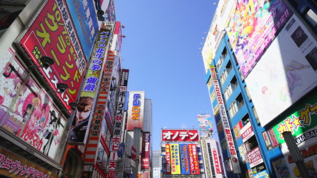 Camera captures many advertisement signs and Billboards of Game soft shops, Anime shops and Electric shop at front of Akihabara Station.