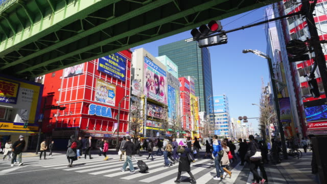 Camera captures many Game soft shops and Anime shops along the Chuo Dori at crosswalk under the JR Line in Akihabara, Chiyoda-ku Tokyo.