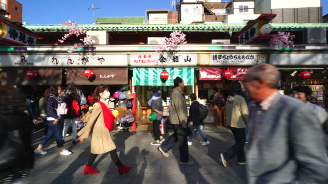 tl camera captures many people and traditional gift shops along the nakamise-dori at sensoji temple (asakusa kannon temple). - temple building stock videos & royalty-free footage