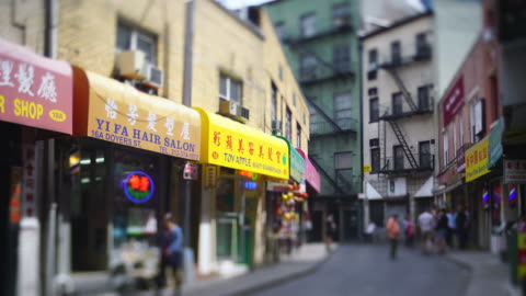 camera captures many signboards of stores, chinese restaurants, vegetable store etc. along the narrow street among the rows of buildings in chinatown at new york city ny usa on may 22 2019. - chinatown stock videos & royalty-free footage