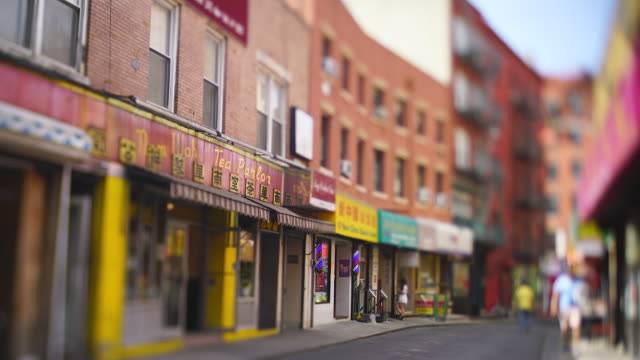 vídeos de stock e filmes b-roll de camera captures many signboards of stores, chinese restaurants, vegetable store etc. along the narrow street among the rows of buildings in chinatown at new york city ny usa on may 22 2019. - tilt shift