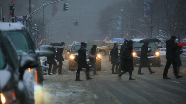 Camera captures Midtown Manhattan Traffic and commuters while snowing at Park Avenue while snowing.