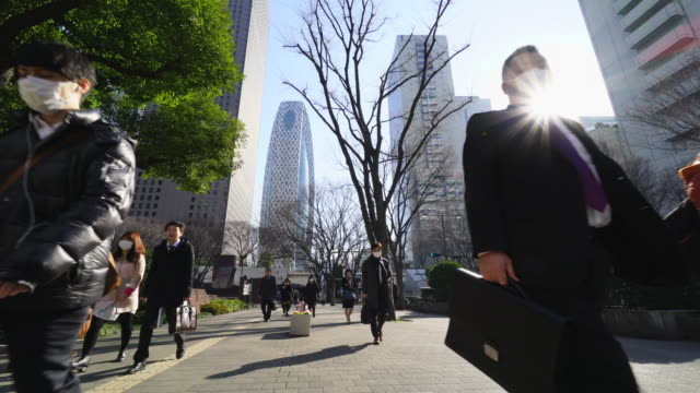 camera captures morning commute scene at shinjuku subcenter business district. - hauptverkehrszeit stock-videos und b-roll-filmmaterial