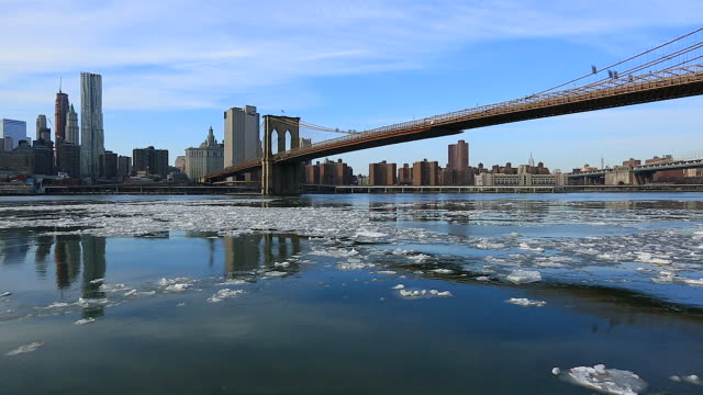 camera captures moving drift ice and reflections of manhattan skyscrapers beside the brooklyn bridge at east river. - 流氷点の映像素材/bロール