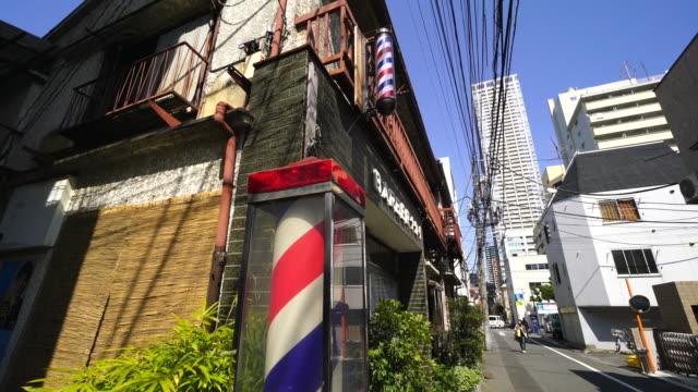 Camera captures neon sign of Barber Shop at back alley in Tsukishima Tokyo.