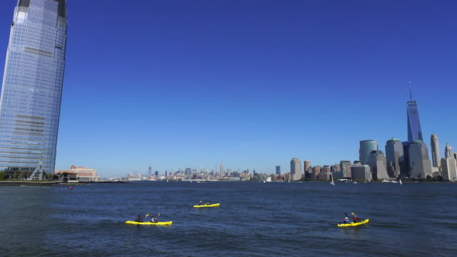 PAN Camera captures New Jersey waterfront high-rise residential buildings and kayaks from Liberty State Park. Manhattan skyscrapers can be seen at opposite shore of Hudson River.