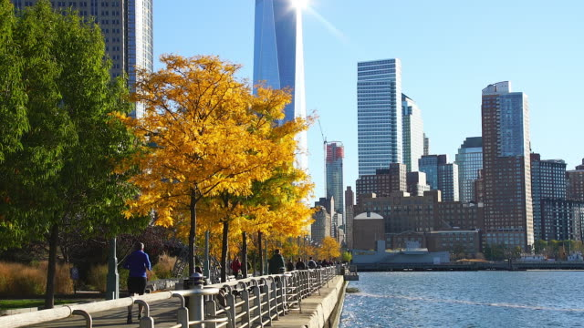 camera captures one world trade center and other skyscraper behind autumnal leaves trees. people walk down the promenade beside hudson river. - promenade stock videos & royalty-free footage