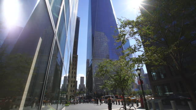 TU Camera captures One World Trade Center and reflected buildings to window, which are illuminated by the sun. People walk on the sidewalk and cars run on street.